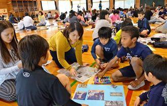 親と意見交換をしながら切り抜き新聞を作る子どもたち=宜野湾市立普天間第二小学校