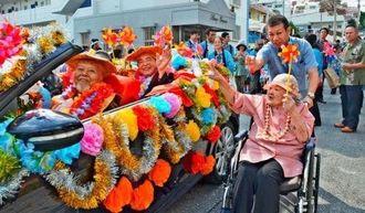 オープンカーに乗ってパレードする知念明さん(左端)と玉城祥太郎さん(同2人目)=17日、浦添市屋富祖