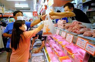 旧盆の準備で豚肉などの食材を買い求める人たち=30日午前、那覇市松尾・第一牧志公設市場(金城健太撮影)