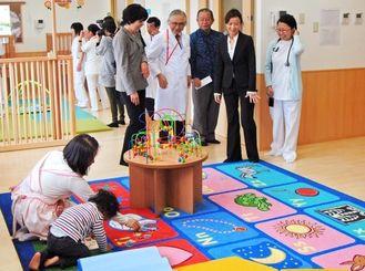 県立中部病院内の「おひさま保育園」を見学する病院関係者ら=4日午前、うるま市