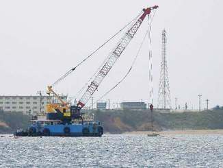 海中にブロックを投入する作業船=24日午前11時ごろ、名護市辺野古沖