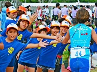 ゴール前にハイタッチで応援する伊是名幼稚園と小学校の子供たち=2013年10月20日、伊是名村