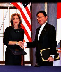 日米地位協定の米軍属についての補足協定にサインし握手する岸田外相(右)とケネディ米駐日大使=16日、都内の外務省・飯倉公館