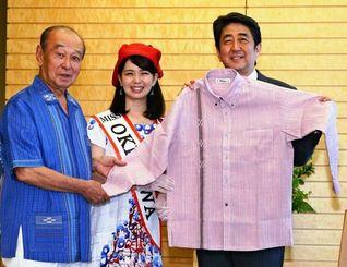 仲井真弘多知事(左)とミス沖縄の名護愛さんから、沖縄の「かりゆし」を贈られ笑顔の安倍首相=26日午前、首相官邸
