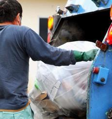 回収したごみをパッカー車に積み込む平良弘明さん。限られた時間内に作業を済まさなければならないため、動きに無駄がない