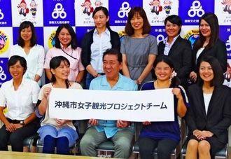桑江朝千夫・沖縄市長(前列中央)を囲み笑顔を見せる「女子観光プロジェクトチーム」のメンバーたち=7月28日、沖縄市役所