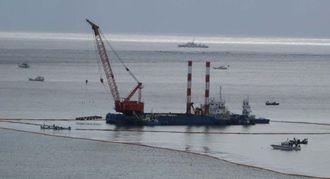 コンクリートブロックの投入作業を続ける大型作業船=1日午前11時半ごろ、名護市の大浦湾