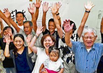 3選を決め、娘を抱いて喜ぶ宮里歩さん(前列中央)=2日午後11時40分ごろ、北谷町桑江