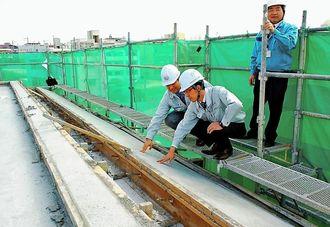 CfFAを混合したコンクリートの状況を確認するゼロテクノ沖縄の担当者ら=浦添市西原の建築現場