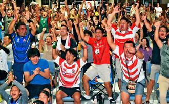 パブリックビューイング会場で、日本のトライに沸き上がるラグビーファン=13日、読谷村地域振興センター(金城健太撮影)