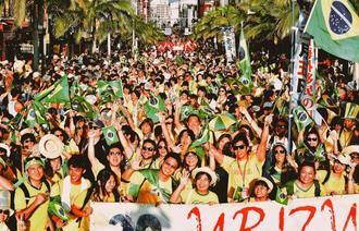 沿道からの声援に笑顔で応えパレードするブラジルからの参加者=26日午後、那覇市・国際通り(金城健太撮影)