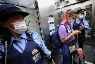 羽田空港で警察官にエスコートされる陸上ベラルーシ代表のクリスツィナ・ツィマノウスカヤ=1日(ロイター=共同)