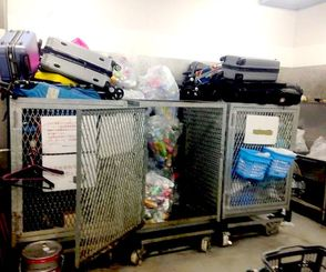 集積場で、空き缶などと一緒に積まれているスーツケースの山=3月、那覇空港国際線ビル(提供)