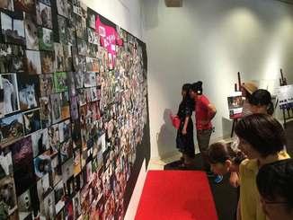 一般の人が撮影した「自慢のねこちゃん写真展」を熱心に見る来場者=浦添市美術館