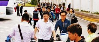 那覇空港国際線ターミナルでバス乗り場に移動する観光客ら=2月、那覇空港国際線ターミナル