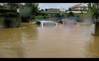 天願川が氾濫し、集落に大量の水が流れ込んだ。車両2台が水につかっていた=7月9日午前9時ごろ、うるま市天願(比屋根真澄撮影)