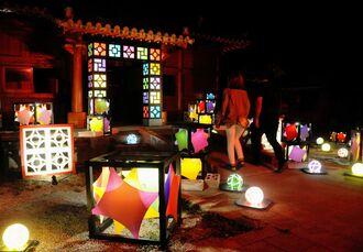 ランタンが鮮やかに彩る施設内を散策する来場者=読谷村の体験王国むら咲むら