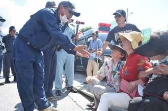 ゲート前で新基地建設に座り込んで抗議する福島瑞穂参院議員(右から2人目)に移動するよう警告する県警=18日午前10時7分、名護市辺野古の米軍キャンプ・シュワブゲート前