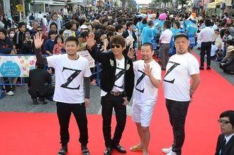 笑顔で手を振る(左から)品川ヒロシさん、哀川翔さん、木村祐一さん、野性爆弾の川島邦裕さん=28日、沖縄市のゲート通り