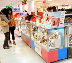 色とりどりのチョコレートやスイーツを眺める買い物客=26日、那覇市久茂地・デパートリウボウ