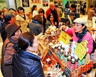 久米島みそなどの特産品を買い求める客でにぎわう会場=タイムスビル