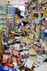 酒販売店で棚から落ちたビール缶などを片付ける店員=18日午前9時40分ごろ、大阪府枚方市