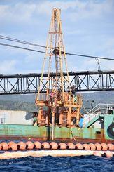 新たな掘削地点で作業船から海に降ろされる掘削棒=19日、名護市辺野古沖の平島付近