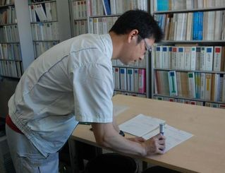 海底ボーリング調査に向けて沖縄防衛局が提出した協議書に収受印を押す県水産課の職員=14日午前9時すぎ、県庁