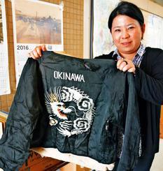 沖縄市に戻ったモーラーさんのジャケットを手に取る市史編集担当の松川さん=沖縄市役所