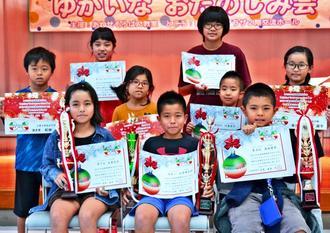 3・4年生の部フラッシュ暗算競技と読上暗算競技で優勝した安里颯太郎さん(前列中央)と、同大会で入賞したあわせそろばん教室の仲間たち=沖縄市福祉文化プラザ