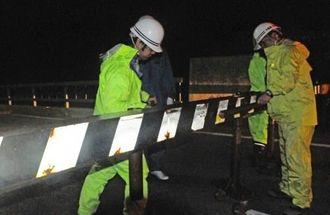 池間大橋の通行を止めるため鋼製のゲートを設置する県宮古土木事務所の職員ら=7日午後8時27分ごろ、宮古島市平良狩俣