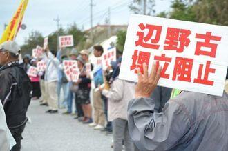 キャンプ・シュワブのゲート前で辺野古新基地建設反対の意思を示す参加者たち=27日午前、名護市