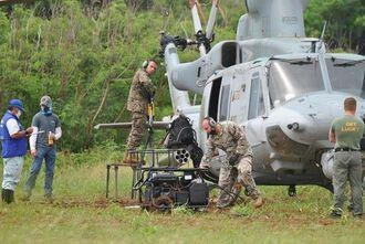 不時着したヘリの周辺の整地作業を行う米兵ら=7日午前10時24分、うるま市の津堅島