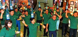 朝礼後、一升瓶を頭に載せて「瓶踊り」の練習をするまさひろ酒造の社員=糸満市西崎町