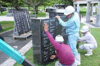 新たな刻銘板がを設置する作業員ら=10日、糸満市摩文仁・平和祈念公園