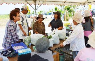 島の人と来場者がとれたての野菜や手作りの食べ物をはさんでおしゃべりや販売を楽しむ=2日、うるま市与那城宮城島のシヌグ堂前