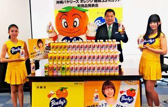 「沖縄バヤリース オレンジ糖類33%カット」をPRする川合社長(右から2人目)=26日、浦添市の同社