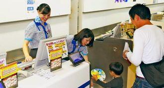 全日空の搭乗手続きカウンターで搭乗手続きなどに携わるエアー沖縄スタッフ=1日午後、那覇空港