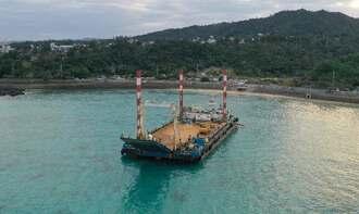 タグボートのロープにけん引されて離岸する座礁船=14日午前7時48分、恩納村名嘉真(小型無人機で撮影)
