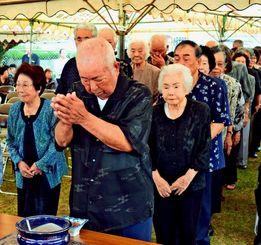 戦没者への祈りをささげる参加者たち=23日、読谷村楚辺の慰霊の塔