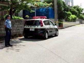 兄が弟を刺した民家の前で待機する警察官=18日午前9時半ごろ、北谷町上勢頭