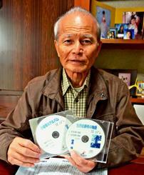 「牡丹社事件の物語」と「小琉球のアルバム」のCDの歌詞に込めた思いを話す吉川安一さん=名護市内