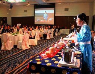 復元した茶葉や茶器を前に、お点前を披露する棚橋篁峰さん(右)=22日、那覇市・ANAクラウンプラザホテル沖縄ハーバービュー