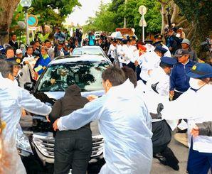 抗議する市民に取り囲まれ、知事公舎を出る県幹部らの乗った公用車=27日午後4時12分、那覇市寄宮