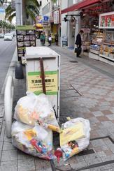 国際通りに捨てられたごみ。不法投棄をしないよう呼び掛けるポスターの前に置かれていた=日午後2時半頃、那覇市の国際通り