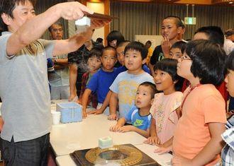 液体窒素の不思議な現象に興味津々な子どもたち=30日午後、 北谷町・ちゃたんニライセンター