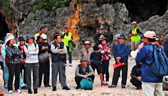ジョン万次郎・沖縄上陸の地の大度浜で説明に耳を傾ける宿道探索ウオーキングの参加者ら=5日、糸満市