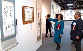 多彩な展示作品に見入る関係者=6日、那覇市民ギャラリー