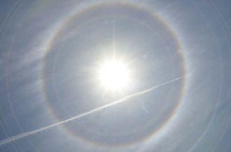 名護市内で確認された日暈現象。飛行機雲が横切った=19日午後0時半すぎ(阿部岳撮影)