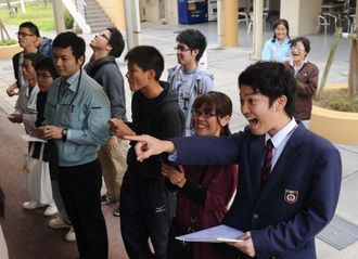 自分の受験番号を掲示板で見つけ、喜ぶ合格者=17日午前11時すぎ、宜野湾市・沖縄国際大学